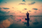 Silhouette young woman practicing yoga — Stock Photo