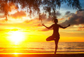 Silhouette woman practicing yoga — Stockfoto