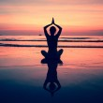Yoga woman sitting on sea coast at sunset. — Stock Photo