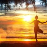 Yoga woman on sea coast at sunset. — Stock Photo