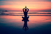 Yoga woman sitting on sea coast at sunset. — Stock Photo