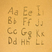 Alphabet written on a sand beach — Stock Photo