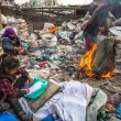 Unidentified child is sitting while her parents are working on dump — Stock fotografie #44952155