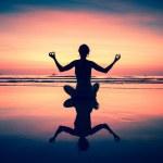 Yoga woman sitting on sea coast at surreal sunset. — Stock Photo #44952443