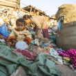 Unidentified child is sitting while her parents are working on dump — Stockfoto #44954395