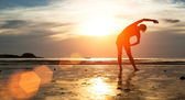 Woman silhouette doing exercise on the beach — Stockfoto