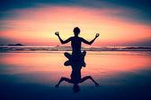 Yoga woman sitting on sea coast at surreal sunset. — Stock Photo