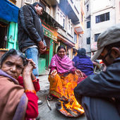 Poor people warm themselves by the fire in the street at slums — Stockfoto