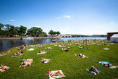 Unidentified people sunbathe on the beach the Peter and Paul Fortress — Stock Photo