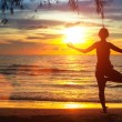 Yoga girl on the beach during sunset. — Stock Photo