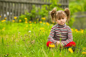 Funny lovely little five-year girl sitting in grass — Stock Photo