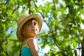 Little girl posing in a straw hat in the park. — Stock Photo