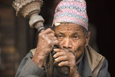 Nepalese man smokes on the street. — Stock Photo