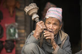 Nepalese man smokes on the street. — Stock Photo