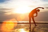 Woman Silhouette exercises on beach — Stock Photo