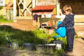 Boy watering  flower bed — Stock Photo
