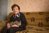 Happy elderly woman with her cat — Stock Photo