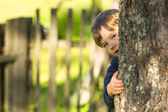 Cute little boy peeking from behind tree — Stock Photo