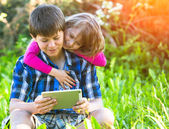 Boy with a tablet PC and his little siste — Stock Photo