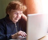 Elderly woman using laptop — Stockfoto