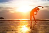 Woman practicing yoga on beach — Stock Photo