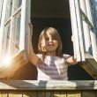 Little girl looks out the window — Stock Photo #49742489