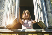 Little girl looks out the window — Stock Photo