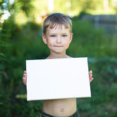 Little boy holding clean paper — Stock Photo
