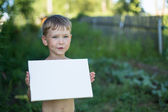 Little boy holding clean sheet paper — Stock Photo
