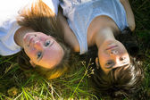 Two young girl lying on grass — Stock Photo