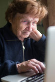 Elderly woman using laptop — Photo