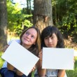 Two girls holding clean white sheet paper — Stock Photo #50638147