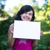Fun girl holding clean white sheet paper — Stock Photo