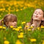Sisters blowing dandelion seeds away — Stock Photo #51311283
