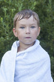 Little boy wrapped in a towel after swimming — Stock Photo