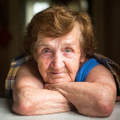 Old woman sitting at table — Stock Photo