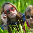Two young sisters lying in the grass — Stock Photo #51398263