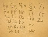 алфавит, написанные на песчаном пляже. — Стоковое фото