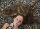 Young girl lying on a stone background. — Stock Photo