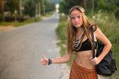 Hippie girl hitchhiking — Stock Photo