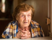 Elderly woman sitting and talk in  house — Stock Photo