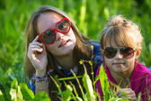 Two young sisters lying in the grass — Stock Photo