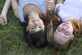 Two young girl lying on grass. — Stock Photo