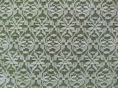 Close-up. Lemon yellow lace fabric with a seamless abstract pattern on a dark blue background. — Stock Photo