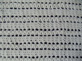 Background. A white handmade knitted cotton fabric with a seamless pattern on a dark-blue background. — Stock Photo