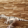 图库照片: Toy plastic predator against stone wall.