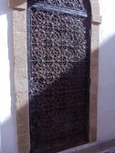 A door with a decorative grating. Medina (old historical part of the town). Essaouira, Morocco. — Stock Photo