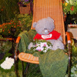 A nice teddy bear in a rocking-chair among plants at the garden exhibition in Moscow. August, 2013. — Stock Photo