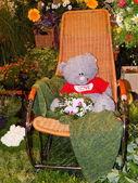 Um ursinho em uma cadeira de balanço entre as plantas do jardim exposições em moscovo. agosto, 2013. — Foto Stock