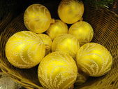 Giocattoli di natale giallo brillante in un cestino. — Foto Stock